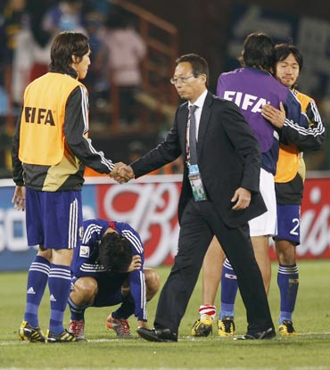 Japan's coach Takeshi Okada consoles his players