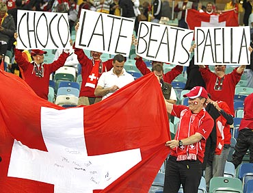 Switzerland's fans hold a national flag and banners as they celebrate after their win against Spain