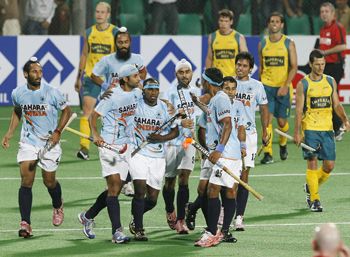 India's Vikram Pillay celebrates with his team mates after scoring the team's first goal during their match against Australia