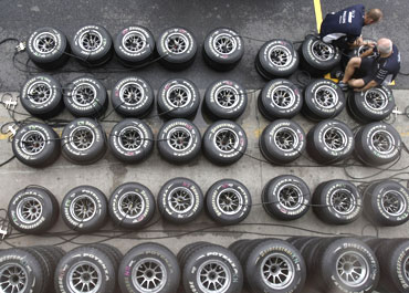 Members of the Williams team check tyres at the Interlagos race track