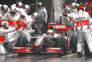 McLaren's Lewis Hamilton gets servicing at the pit lane