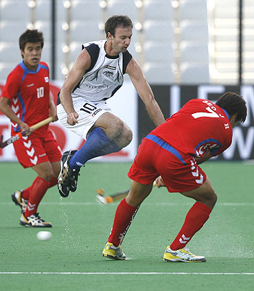 New Zealand's Ryan Archibald (centre) takes evasive action as South Korea's Jong Ho Seo (right) plays a shot