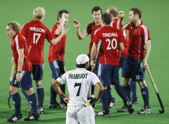 England's players celebrate their first goal as India's Singh watches during their match at the men's Hockey World Cup