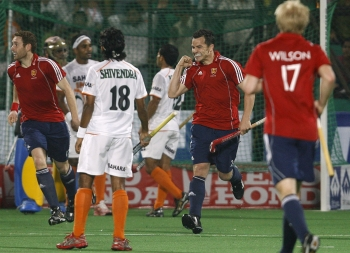 England hockey players celebrate after scoring a goal