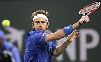 Mardy Fish of the US plays a return during his first round match against Michael Berrer of Germany