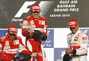Ferrari's Felipe Massa (left) and Fernando Alonso (centre) celebrate their podium finish with McLaren's Lewis Hamilton