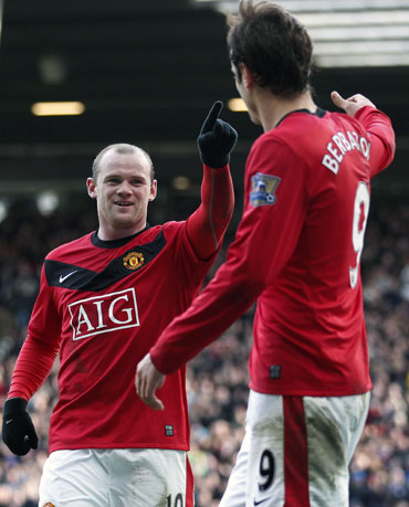 Rooney celebrates with Berbatov after scoring a goal