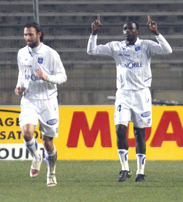 Auxerre's Oliech celebrates with team-mates after scoring against Montpellier