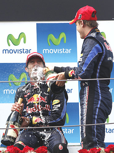 Red Bull Formula One driver Sebastian Vettel of Germany (right) sprays champagne on team-mate Mark Webber of Australia as they celebrate on the podium