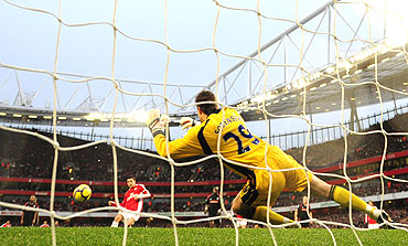Arsenal's Cesc Fabregas (left) takes a penalty kick against Stoke City's goalkeeper Thomas Sorensen