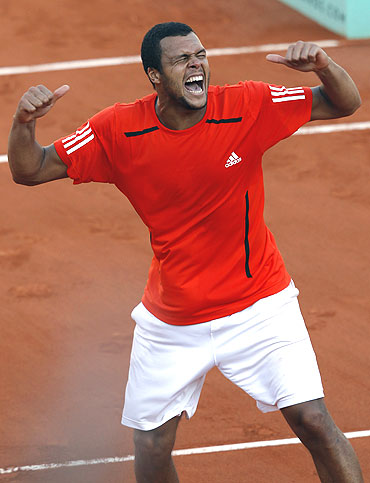Jo-Wilfried Tsonga of France celebrates defeating Daniel Brands of Germany