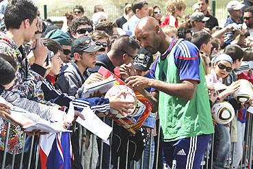 French striker Nicolas Anelka signs autographs after a training session in the French Alps resort of Tignes
