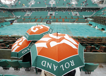 Spectators sit under umbrellas as rain interrupts play at the French Open