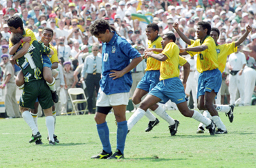 Brazilian striker Bebeto leaps into the arms of goalkeeper Claudio Taffarel as Italy's Roberto Baggio stares at the ground after missing the penalty