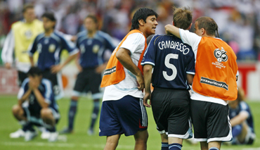 Argentina's Esteban Cambiasso is consoled by team mates after missing during the penalty shootout in the World Cup