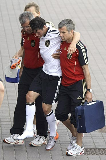Germany's Christian Traesch (2nd from right), is helped by support staff after injuring himself during a match against Suedtirol on Monday