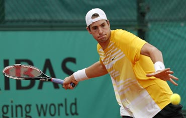 John Isner returns during his match against Marco Chiudinelli