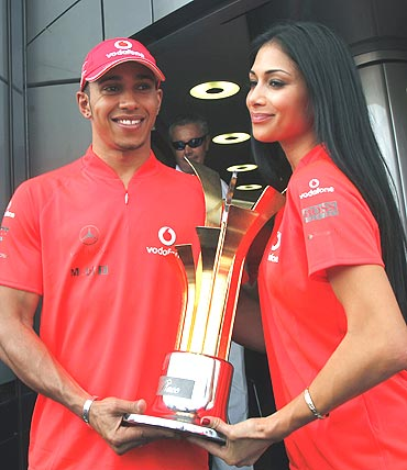 McLaren's Lewis Hamilton (left) and girlfriend Nicole Scherzinger with the trophy