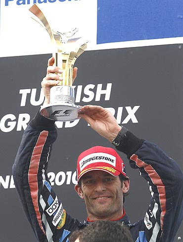 Red Bull's Mark Webber celebrates on the podium after a third place finish