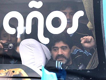 Argentina's national coach Diego Maradona waves to fans from the Argentina team bus, in Buenos Aires, before leaving for South Africa