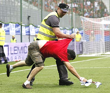 A Serbian supporter is grabbed by a security guard after entering the pitch during the international friendly between Serbia and New Zealand in Klagenfurt
