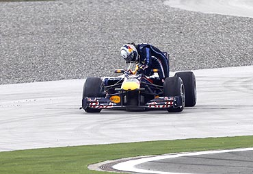 Red Bull's Sebastian Vettel of Germany exits his car after colliding with team-mate Mark Webber