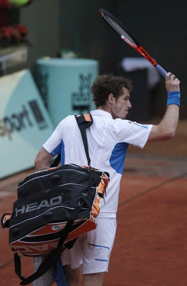 Andy Murray walks back after losing his match to Tomas Berdych