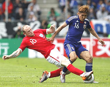 England's Wayne Rooney (left) challenges Japan's Yoshito Okubo during their international friendly in Graz, Austria
