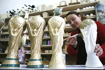 Denise Riquelme, the owner of a shop of handmade crafts, paints replicas of the World Cup trophy in Valparaiso city, near Santiago, Chile