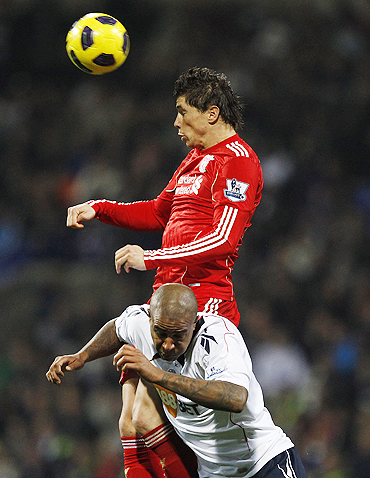 Bolton Wanderers' Zat Knight challenges Liverpool's Fernando Torres (top) during their match on Sunday