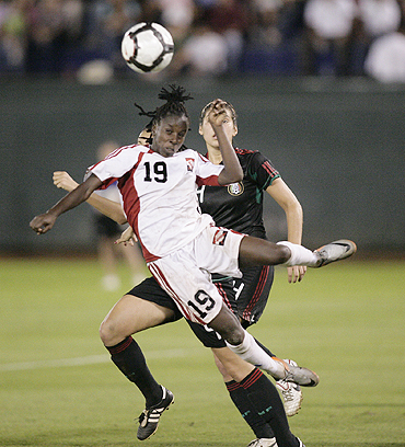 Kennya Cordner of Trinidad and Tobago (left) jumps for the ball over Natalie Vinti of Mexico during the CONCACAF Women's World Cup qualifying match at the Beto Avila stadium in Cancun on Sunday