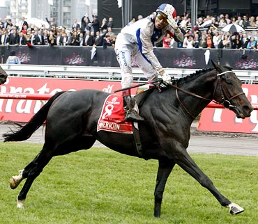 Jockey Gerald Mosse of France celebrates as he rides Americain to victory in the Melbourne Cup