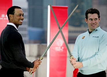 Tiger Woods (left) and Lee Westwood of Britain pose with swords during a promotional event