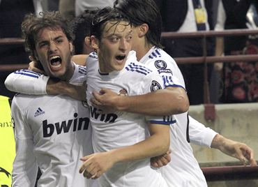 Real Madrid's Pedro Leon (L) celebrates with his team mates after scoring against AC Milan