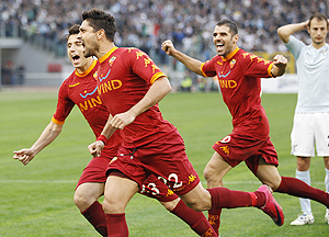 AS Roma's Marco Borriello (centre) celebrates with teammates Simone Perrotta (right) and Leandro Greco after scoring against Lazio on Sunday