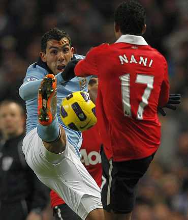 Man City's Carlos Tevez fights for the ball with Man United's Nani