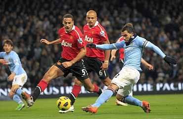 Man City's Carlos Tevez fights for the ball with Man United's Rio Ferdinand