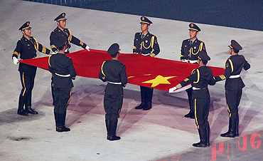 Soldiers hold the Chinese national flag during the opening ceremony