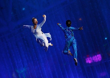 Performers are suspended from a harness during a performance at the opening ceremony