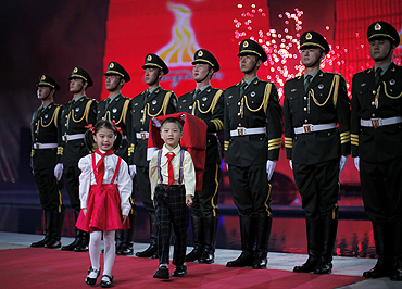 Two children walk away after handing China's national flag to the soldiers during the opening ceremony