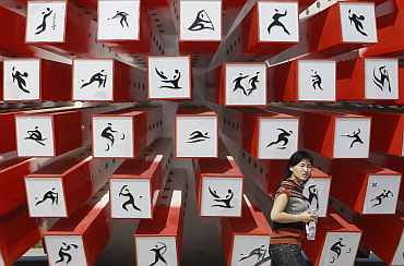 A woman walks past an installation depicting sporting events at the Athletic stadium for the Asian Games in Guangzhou