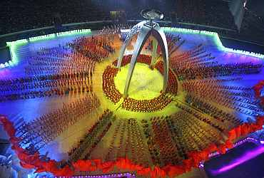 Participants perform near the torch for the Asian Games during a rehearsal for its opening ceremony