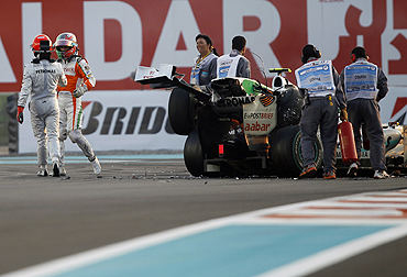 Mercedes's Michael Schumacher walks away from his car after crashing with Force India's Tonio Liuzzi during the Abu Dhabi F1 Grand Prix at Yas Marina circuit on Sunday