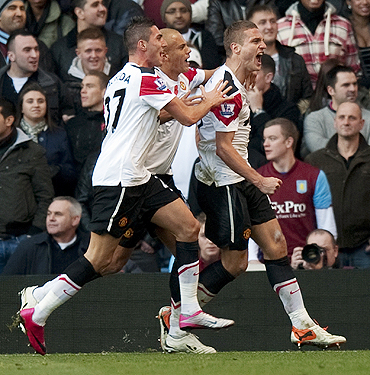Vidic celebrates with teammates after scoring against Aston Villa on Saturday