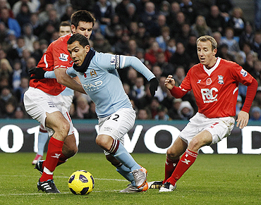 Manchester City's Tevez is challenged by Birmingham City's Scott Dann and Lee Bowyer on Saturday