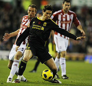 Stoke City's Danny Collins challenges Liverpool's Fernando Torres during their match on Saturday