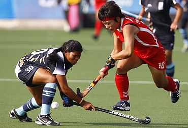 South Korea's Park battles for the ball with India's Pradhan during their hockey game