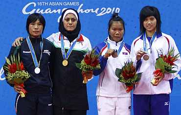Sandhyarani Devi (left) stands on the podium after winning her silver in Wushu