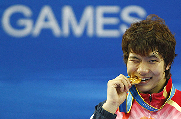 South Korea's Heo Jung-nyoung bites his gold medal after the men's taekwondo 87kg final on Thursday