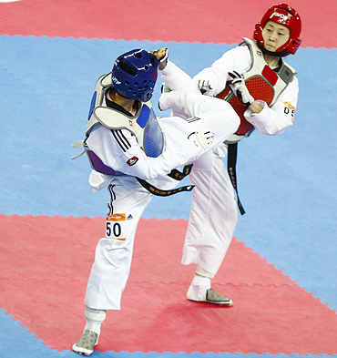 China's Hou Yuzhuo (blue) fights South Korea's Lee Sung-hye during their women's taekwondo under 57k